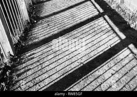 Interesting perspective on shadows made from a fence against a gravel ground.