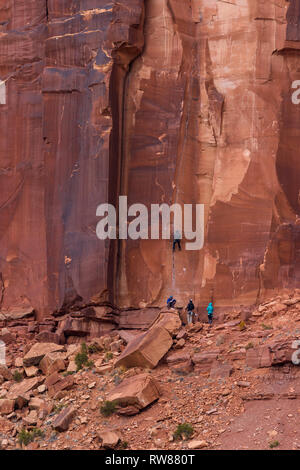 Large red rock butte in characteristic of the American southwest with a group of unrecognizable people climbing the red rock face - Stock Photo