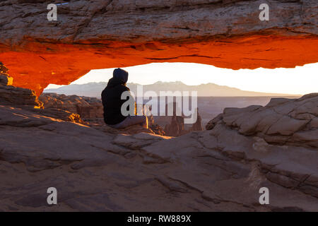 Man sitting on the edge of the cliff as the sun rises across the canyon with Mesa Arch framing the scene - Stock Photo