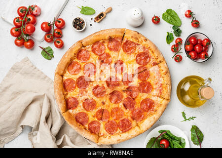 Tasty Pepperoni Pizza On White Background. Pizza, Olive Oil, Cherry tomatoes, Green Leaf Salad Mangold, Arugula and Pepper. Table top view - Stock Photo