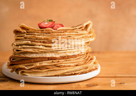 Thin pancakes, blini or crepes on wooden background with copy space for text. Traditional Russian cuisine, Maslenitsa food - Stock Photo