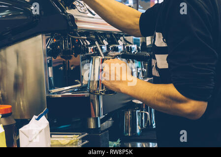Coffee barista at work. Making cappuccino or latte on a coffee machine in an outdoor coffee shop. - Stock Photo