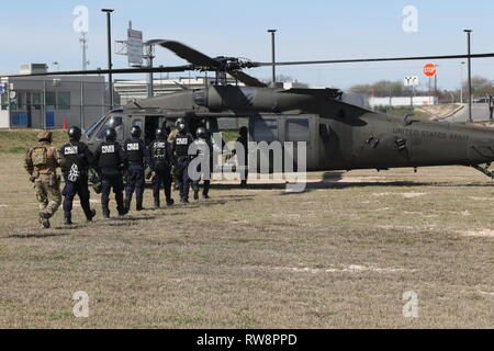 Mobile Field Force officers and Special Response Teams with Customs and Border Protection board a UH-60 Blackhawk helicopter assigned to Company A, 4th Battalion, 3rd Combat Aviation Brigade after conducting joint training with U.S. Army Soldiers at the Del Rio - Ciudad Acuña International Bridge in Del Rio, Texas, Feb 13. The Department of Defense has deployed units across the Southwest Border at the request of U.S. Customs and Border Protection and is providing logistical, engineering, situational awareness and force protection functions. (U.S. Army Photo by Pfc. Joshua Cowden) - Stock Photo