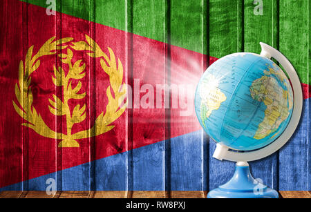 Globe with a world map on a wooden background with the image of the flag of Eritrea. The concept of travel and leisure abroad. - Stock Photo