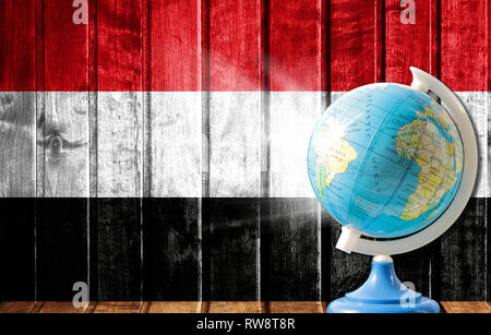 Globe with a world map on a wooden background with the image of the flag of Yemen. The concept of travel and leisure abroad. - Stock Photo
