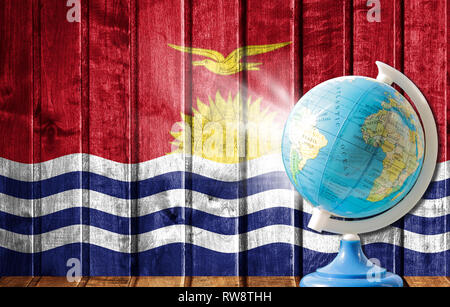 Globe with a world map on a wooden background with the image of the flag of Kiribati. The concept of travel and leisure abroad. - Stock Photo