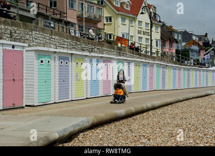 Young woman pushing child in pushchair on the seafront of Lyme Regis, UK; row ow pastel coloured beach huts in the background. - Stock Photo