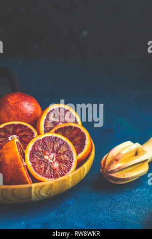 Sliced and whole Sicilian Blood oranges fruits in wooden plate and juicer over dark blue concrete table surface. Dark rustic style. - Stock Photo