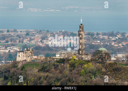The Nelson Monument on Calton Hill photographed from Salisbury Crags on a sunny day, Edinburgh, Scotland - Stock Photo