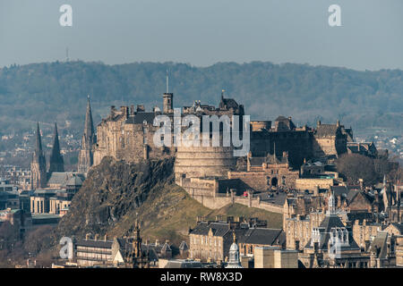 A scenic view of Edinburgh castle and cityscape from Salisbury Crags on a sunny day, Scotland