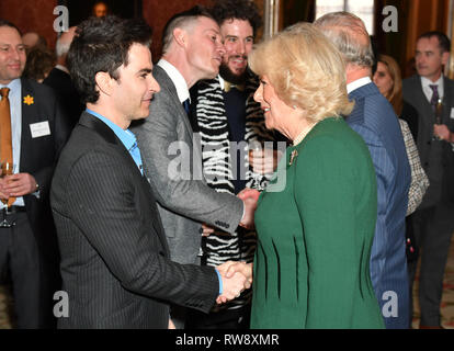 The Duchess of Cornwall speaks with Kelly Jones, lead singer of the Stereophonics, at a reception at Buckingham Palace in London to mark the fiftieth anniversary of the investiture of the Prince of Wales. - Stock Photo