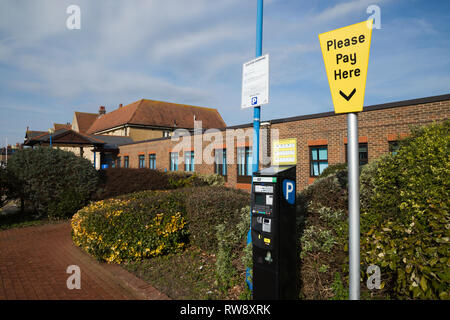 Pay and display ticket machine / pay point with Please Pay Here sign for car parking in car park at NHS Gosport War Memorial Hospital. Hampshire. UK. - Stock Photo