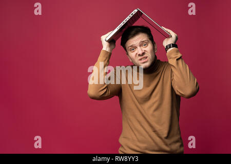 Portrait of unhappy stressed young bearded man holding laptop above head while stsanding isolated over pink background. - Stock Photo