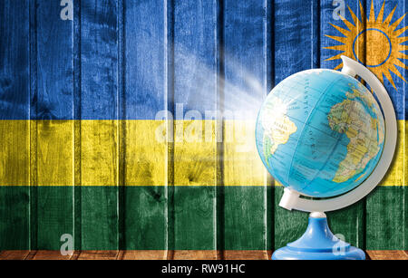 Globe with a world map on a wooden background with the image of the flag of Rwanda. The concept of travel and leisure abroad. - Stock Photo