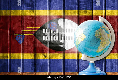 Globe with a world map on a wooden background with the image of the flag of Swaziland. The concept of travel and leisure abroad. - Stock Photo