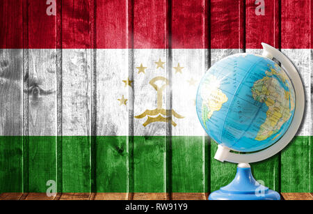 Globe with a world map on a wooden background with the image of the flag of Tajikistan. The concept of travel and leisure abroad. - Stock Photo