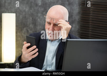 a senior businessman using  smartphone, he is having difficulties and vision problems - Stock Photo