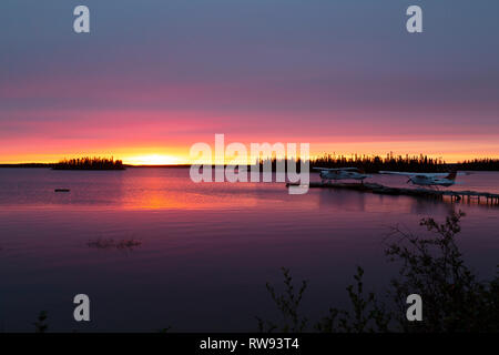 A float plane at the end of a jetty in Egenolf Lake in northern Manitoba, Canada. The lake is seen at sunrise. - Stock Photo