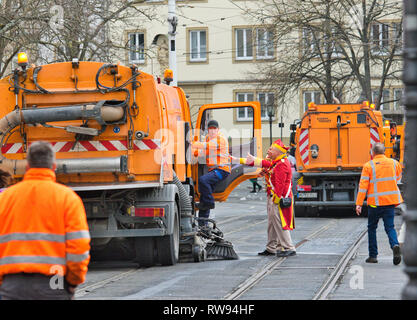 Wurzburg, Germany - 3 March 2019: workers cleaning dirty roads and city with automated cleaning trucks after the events of Fasching cultural carnival. - Stock Photo
