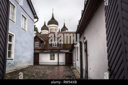 Tallinn old city street in dull, murky rainy evening, with Alexander Nevsky Cathedral domes against grey sky. Alley in Old Tallinn with wet cobbleston - Stock Photo