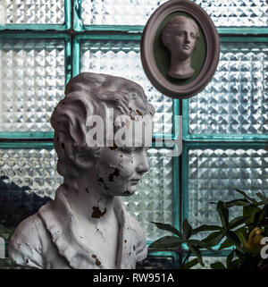 Chipped white head sculpture against glass block wall with antique plaster head molding. Vintage concept. - Stock Photo