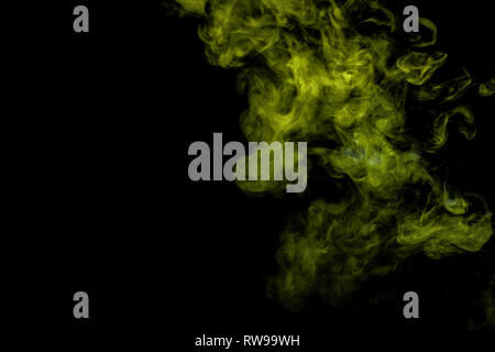 Abstract art blue and green colored smoke on black isolated background. Stop the movement of multicolored smoke on dark background