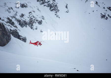 Modern medical helicopter flying in high mountains after picking up an injured skier - Stock Photo
