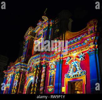 The colourful baroque style facade of the Jesuit Compania de Jesus church in the city center of Quito during a light festival, Ecuador. - Stock Photo