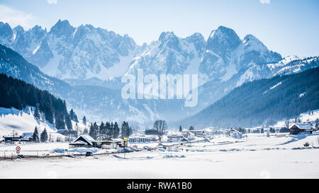 Beautiful white winter snow scene of the Austrian village of Gosau with snowcapped mountains in the distance - Stock Photo