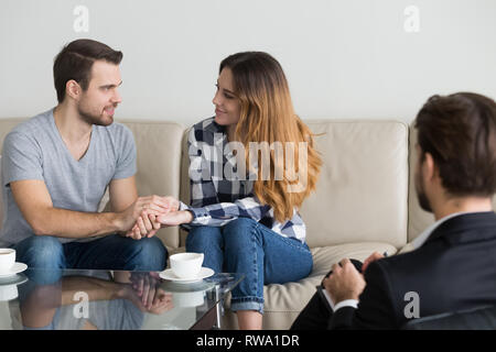 Happy reconciled couple holding hands satisfied with family therapy session - Stock Photo