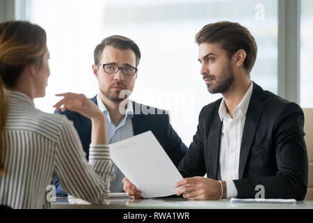Skeptical male hr managers unconvinced about hiring female candidate - Stock Photo