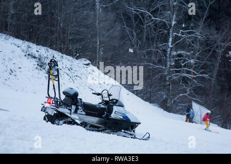 snow bike on a hillside on the ski run in the evening - Stock Photo