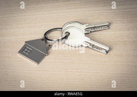 keys and keychains in the shape of a house on a wooden background - Stock Photo
