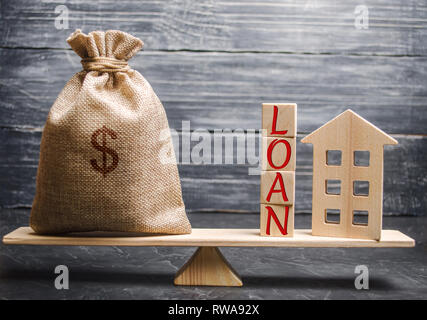 Wooden house and a bag with the word Loan on the scales. Buying a home in debt. Loan for a mortgage. Successful debt repayment. Family investment in r - Stock Photo