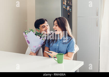 Young man gifting bouquet of flowers to his girlfriend in kitchen. Happy couple hugging. Romantic surprise at home - Stock Photo