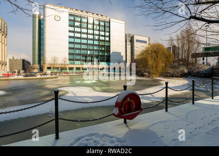 London, England - Feb 2018. Fresh snow covers the frozen pond next to East India DLR station in Poplar. In the background the Global Switch building. - Stock Photo