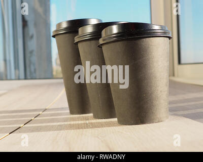 Cups of coffee different sizes on cafe table near window. - Stock Photo