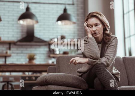 Blonde woman wearing grey sweater feeling sick and depressed - Stock Photo