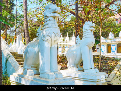 The white statues of chinthe (leogryphs, royal lions) in garden a the entrance to Shwethalyaung Buddha Temple, Bago, Myanmar. - Stock Photo