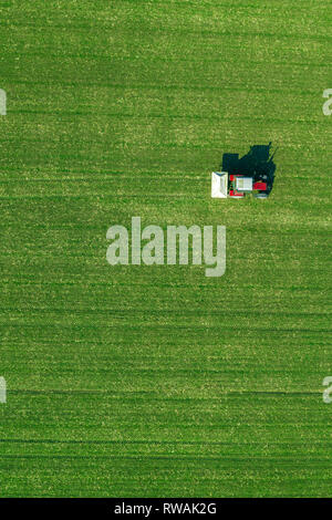 Agricultural tractor is fertlizing wheat crop field with NPK fertilizers, aerial view from drone pov - Stock Photo