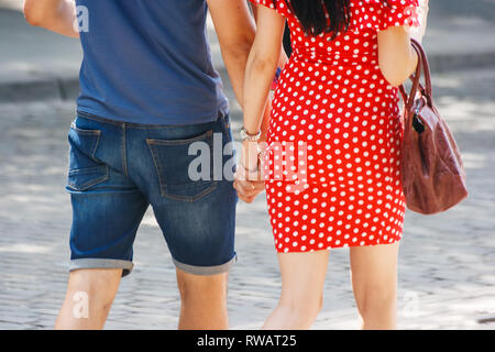 young couple walking down the street holding hands on sunny summer day - Stock Photo