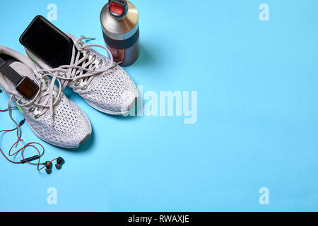 Running shoes with technological accessories and next to a boat of water on a blue background - Stock Photo