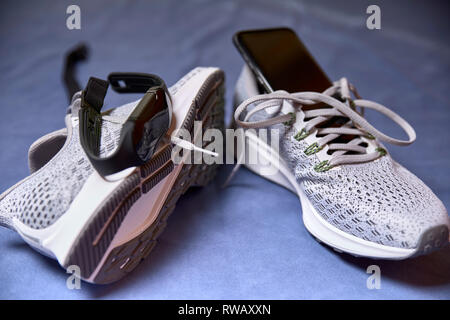 running shoes with technological accessories and next to a pot of water on a blue towel - Stock Photo