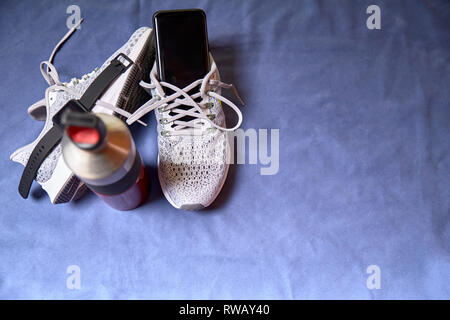 Running shoes with technological accessories and next to a water bottle on a blue towel - Stock Photo