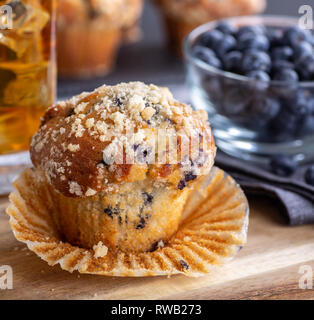 Closeup of a blueberry muffin with muffins, a bowl of berries and a drink in background - Stock Photo