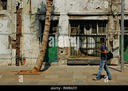 A male photographer is walking in the street of Kota Tua Jakarta, Indonesia. - Stock Photo