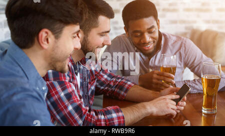 Best friends using smartphone and drinking beer - Stock Photo