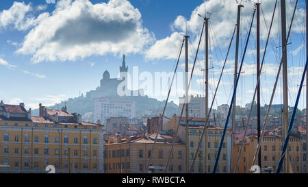 The Old Port Vieux Port of Marseille with Basilique Notre-Dame de la Garde blurred in the fog and the yauchts and boats - Stock Photo