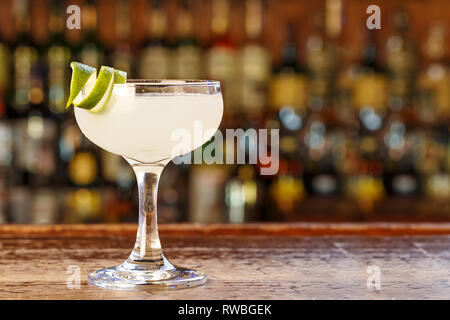 Cocktail daiquiri with ice on the blurred background of the bar, space for text in the menu - Stock Photo