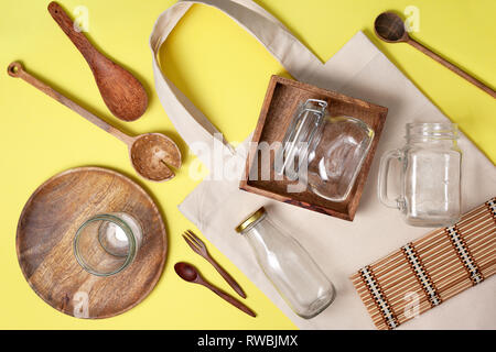 zero waste concept. eco-friendly kitchen set for cooking and storage of products. eco bag, glass jars for storage, wooden dishes on a yellow backgroun